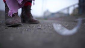 Feche acima de um vidro que deixa de funcionar no asfalto ao lado das botas sujas de uma pessoa desabrigada Os fragmentos de vidr filme