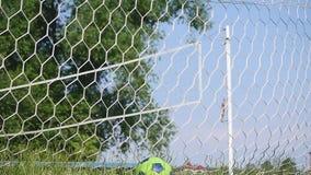 Feche acima de uma bola de futebol que bate uma rede vídeos de arquivo