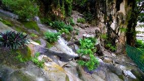 Feche acima de uma cachoeira pequena com água que espirra na pedra no rio 4K de Malásia video estoque