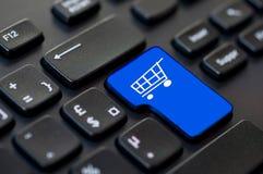 Feche acima de uma chave do retorno azul com um ícone do carrinho de compras no computador Fotografia de Stock Royalty Free
