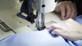 Feche acima de uma costureira que costura uma camisa em uma fábrica filme