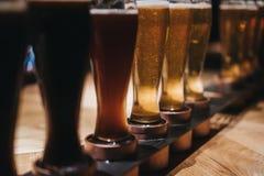Feche acima de uma cremalheira dos tipos diferentes das cervejas, escuros para iluminar-se, em uma tabela fotos de stock royalty free
