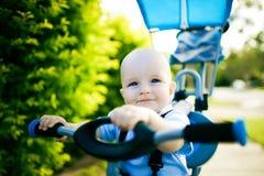 Feche acima de uma criança feliz que senta-se na bicicleta imagens de stock