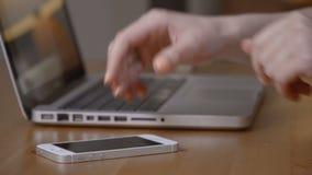 Feche acima de uma datilografia ocupada das mãos da fêmea em um portátil video estoque