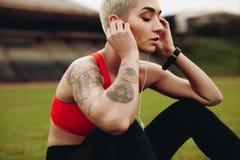 Feche acima de uma escuta de relaxamento do atleta fêmea a música fotografia de stock royalty free
