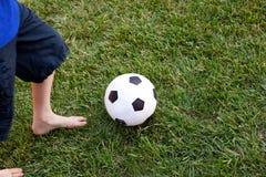 Feche acima de uma esfera e de um jogador de futebol Fotografia de Stock