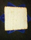 Feche acima de uma folha do matzoh na placa azul foto de stock