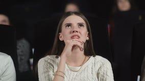 Feche acima de uma jovem mulher assustado que usa suas mãos para cobrir sua cara ao olhar um filme assustador vídeos de arquivo