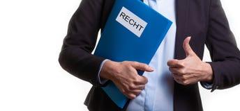 Feche acima de uma jovem mulher em um terno de negócio que guarda um arquivo com um texto alemão: LEI imagens de stock