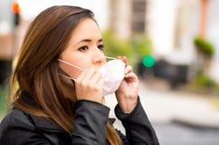 Feche acima de uma jovem mulher que veste uma máscara protetora na rua na cidade com poluição do ar, fundo da cidade fotos de stock