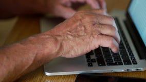 Feche acima de uma mão aposentada que trabalha com um teclado de computador Internet banking, portátil, dispositivos modernos e p filme