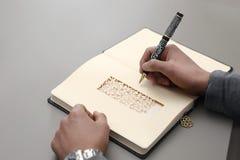 Feche acima de uma mão da escrita do homem em um caderno Imagens de Stock Royalty Free