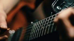 Feche acima de uma mão do homem que joga cordas de uma colheita da guitarra Movimento lento vídeos de arquivo