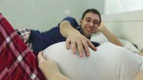 Feche acima de uma mão do ` s do homem que afaga uma barriga grande de uma mulher gravida vídeos de arquivo