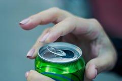 Feche acima de uma mão que abre uma bebida imagem de stock