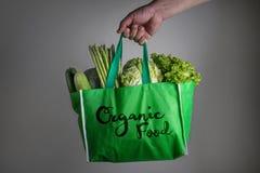 Feche acima de uma mão que guarda o saco de mantimento verde com texto do alimento biológico imagens de stock royalty free