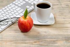 Feche acima de uma maçã vermelha madura para o petisco do escritório no desktop de madeira Fotografia de Stock Royalty Free