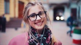 Feche acima de uma menina atrativa nova com direito bonito de sorriso para a câmera, penteado ocasional dos fones de ouvido feliz filme