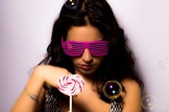 Feche acima de uma menina bonita com bolhas de sabão de sopro da composição profissional em torno dela Fotografia de Stock