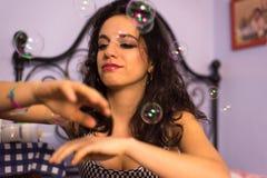 Feche acima de uma menina bonita com bolhas de sabão de sopro da composição profissional em torno dela Imagem de Stock