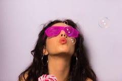 Feche acima de uma menina bonita com bolhas de sabão de sopro da composição profissional em torno dela Foto de Stock Royalty Free
