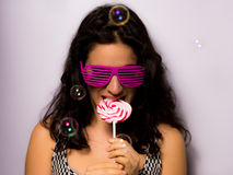 Feche acima de uma menina bonita com bolhas de sabão de sopro da composição profissional em torno dela Fotografia de Stock Royalty Free