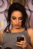 Feche acima de uma menina bonita com a composição profissional que olha seu telefone Fotografia de Stock Royalty Free