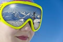 Feche acima de uma menina com uma reflexão da máscara de esqui um landscap nevado da montanha Fotos de Stock Royalty Free