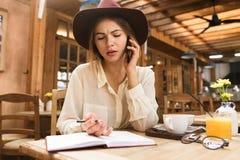 Feche acima de uma menina confusa no chapéu que senta-se na tabela do café dentro, falando no telefone celular, tomando notas em  foto de stock royalty free