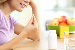 Feche acima de uma menina que toma o comprimido da vitamina Imagens de Stock