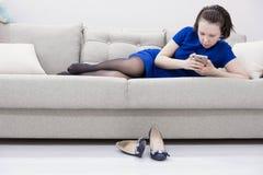 Feche acima de uma menina relaxado que usa um telefone esperto que encontra-se em um sofá na sala de visitas em casa com um fundo fotografia de stock royalty free