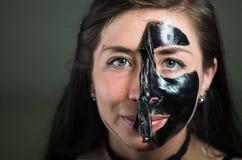 Feche acima de uma metade da descolagem da jovem mulher da beleza de uma máscara protetora preta Fotos de Stock Royalty Free