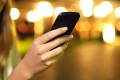 Feche acima de uma mão da mulher usando um telefone esperto na noite Fotografia de Stock Royalty Free