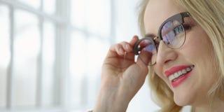 Feche acima de uma mulher bonita nova com vidros na janela foto de stock