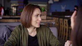 Feche acima de uma mulher bonita nova que senta-se no restaurante e que passa o tempo na sociedade de seus amigos adorable video estoque