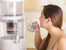 Feche acima de uma mulher bonita que bebe um vidro da água com um sistema do filtro de purificador da água em um fundo da cozinha foto de stock royalty free