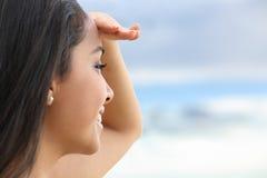 Feche acima de uma mulher bonita que olha o horizonte com uma mão na testa Imagem de Stock