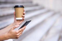 Feche acima de uma mulher de negócios que usa o telefone celular e guardando o copo de papel Foto de Stock Royalty Free