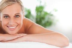 Feche acima de uma mulher de sorriso que relaxa em um lounger Fotos de Stock Royalty Free