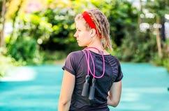 Feche acima de uma mulher desportivo nova com um jumprope sobre um ombro fotos de stock royalty free