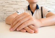 Feche acima de uma mulher na roupa ocasional com suas mãos abraçadas dentro Imagens de Stock Royalty Free