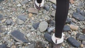 Feche acima de uma mulher que anda com sapatas de Brown e a calças preta sobre pedras litorais vídeos de arquivo