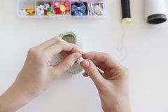 Feche acima de uma mulher que costura uma sapata de bebê com uma agulha Fotografia de Stock Royalty Free