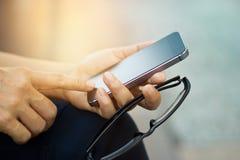 Feche acima de uma mulher que usa o telefone esperto móvel exterior e os vidros fotografia de stock royalty free