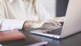 Feche acima de uma mulher que veste uma camisa branca que datilografa e que usa um touchpad do portátil em um escritório Fotografia de Stock Royalty Free