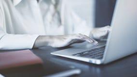 Feche acima de uma mulher que veste uma camisa branca que datilografa e que usa um touchpad do portátil em um escritório Imagem t Fotos de Stock Royalty Free