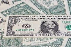 Feche acima de uma nota do dólar em outras notas de um dólar Fotos de Stock