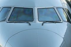 Feche acima de uma opinião dianteira da cabina do piloto do avião do jato da janela do avião com limpadores de para-brisa imagem de stock