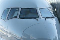 Feche acima de uma opinião dianteira da cabina do piloto do avião do jato da janela do avião com limpadores de para-brisa fotografia de stock