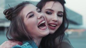 Feche acima de uma opinião duas moças com a composição bonita que vai louca, riso, abraçando Beleza natural, desgaste das calças  filme